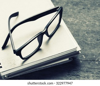 Glasses with note book on wood background.black and white color tone style.