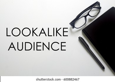 A glasses, notebook and pen with LOOKALIKE AUDIENCE written on white background. A business concept.