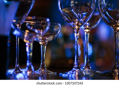 Glasses on the bar counter during a party. Transparent clean glasses in neon light on the bar prepared for drinks. Festive party in a nightclub. Soft selective focus, toning and beautiful bokeh.
