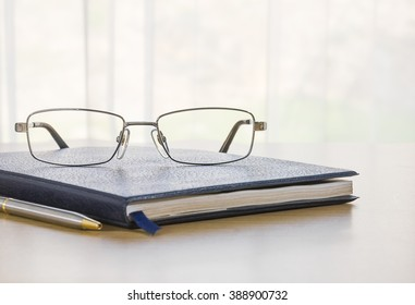 Glasses on a book with on the desk by nature background