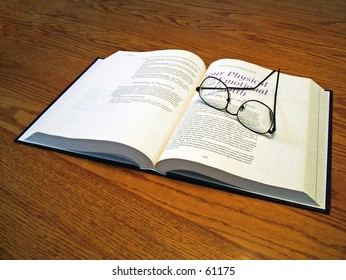 Glasses on a book that is on an oak desk.