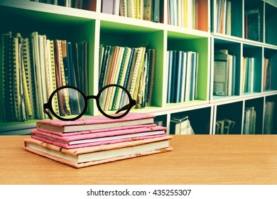 glasses on books with blur perspective bookshelf background