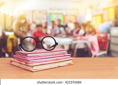 glasses on books with blur student in classroom background