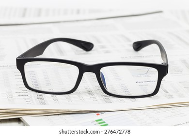 Glasses on business newspapers