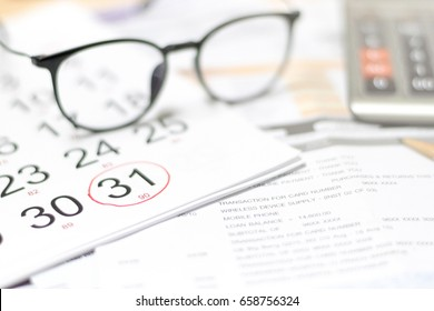 Glasses on credit card statement and calendar highlight on last day of month as due date and blur calculator