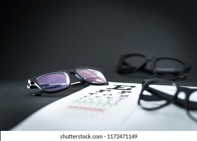 Glasses on eye sight test chart with different spectacle options on optician table. Ophthalmology or optometry clinic. Vision, eyesight and health care concept.