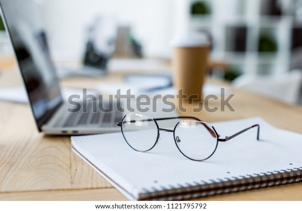 glasses on notebook and coffee to go on wooden table in office