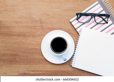 Glasses on the notebook and  a cup of coffee on wooden table