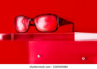 glasses on a plexiglass display with red background