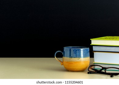 Glasses on stack of books and a cup of coffee on wooden table. Education concept.