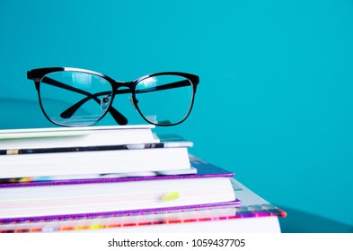 Glasses on a stack of books in the interior in a minimalist style. Monocolor. The concept of reading, education, buying books.