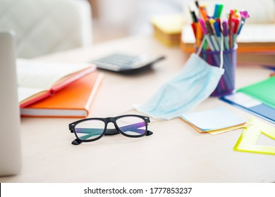 Glasses are on the table among school supplies, books, laptop, protective mask. Preparing for distance learning. Back to school. Working environment on the Desk at home.
