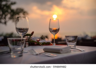 glasses on a table in a cafe on the background of the setting sun
