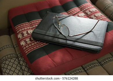 A glasses on a tablet on a cushion