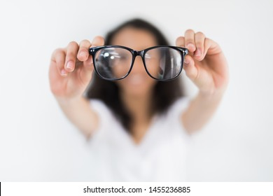 Glasses - optician showing eyewear. Closeup of glasses, with glasses and frame in focus. Woman optometrist on white background.