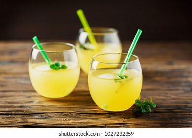 Glasses of orange cocktails with ice and mint, wooden table and selective focus