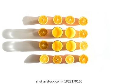 Gläser aus Orangensaft mit gehackten Orangen auf weißem Hintergrund mit großen, schönen Schatten von der Sonne