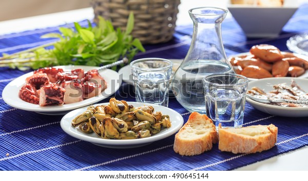 Glasses of ouzo and appetizers