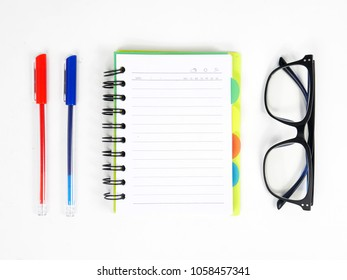 Glasses, pen and note book on white background.