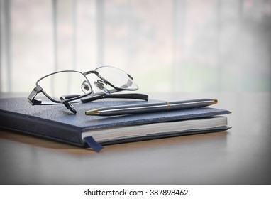 Glasses and pen on a book and table with nature background