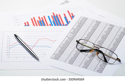 Glasses and pen on financial report