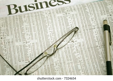 Glasses and a pen resting on a stock market report