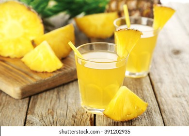 Glasses of pineapple juice on a grey wooden table