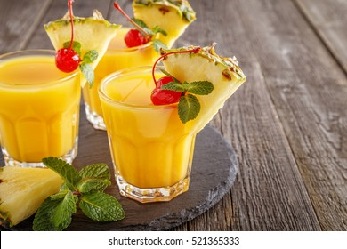 Glasses of pineapple juice with pieces of pineapple, cocktail cherry  and mint on wooden table, healthy drink concept.