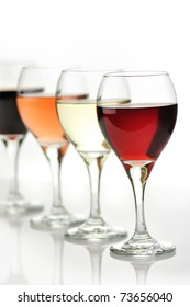 glasses of pink , red  and white wine on white background