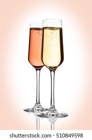 Glasses of pink  and yellow champagne on pink with bubbles on pink background