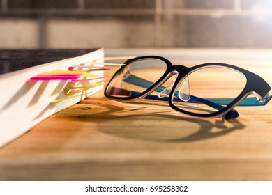 Glasses placed beside the book on the desk.