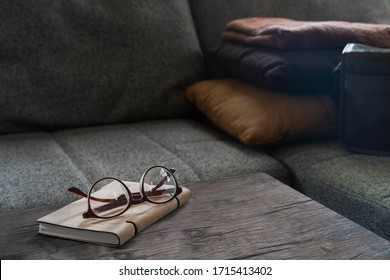 a glasses is placed on a leather book,  leather book is on brown wooden table in living room in front of gray fabric sofa that has brown and orange pillow.