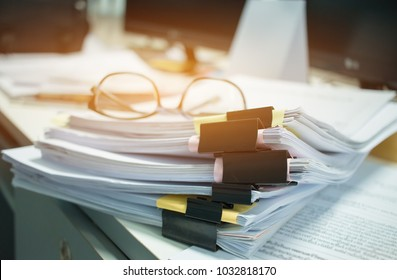 Glasses placed on Unfinished documents stacks of paper files on computer desk for report , piles of unfinished papers achieves with clips, Business offices concept. Document is written,drawn,presented