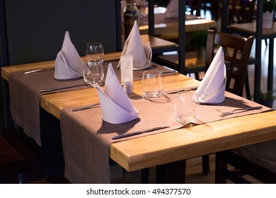 Glasses, plates and silverware on table in restaurant - food background