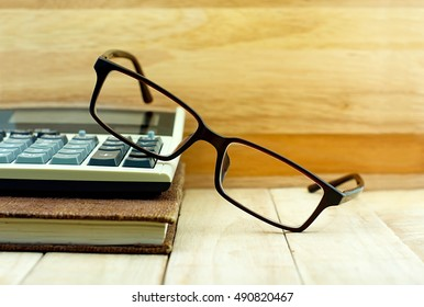 Glasses put on calculator and brown color notebook on wooden table. Education concept.