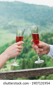 Glasses with red champagne drink in bride and groom hands. Happy newlyweds drinking. Loving couple created new family.