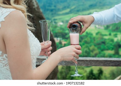 Glasses with red champagne drink. groom pouring wine. Happy newlyweds drinking. Loving couple created new family.