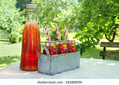 Glasses of red strawberry juice with striped straws in green summer garden