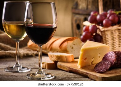 Glasses of red and white wine with cheese, grape and salami on a wooden background.