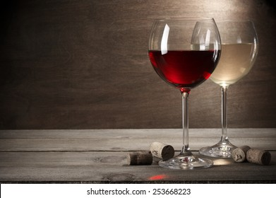 Glasses of red and white wine with corks on rustic wooden background with copy space.