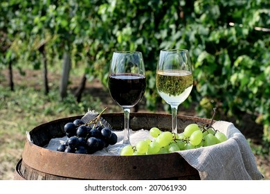 Glasses of red and white wine with grapes on the barrel. Selective focus