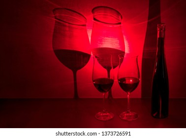 Glasses of red wine (Beaujolais nouveau) cast shadow on gray background with red light