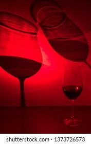 Glasses of red wine cast shadow on gray background with red light