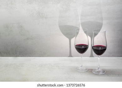 Glasses of red wine cast shadow on gray background