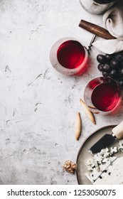 Glasses of red wine, cheese and grapes on rustic concrete backgr