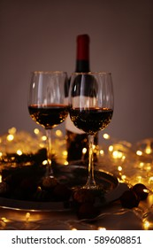 Glasses of red wine and chocolate truffles on decorated table closeup