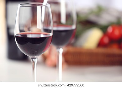 Glasses of red wine with food on table closeup