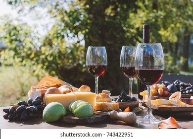 glasses red wine with fruits and cheese on wooden table outdoors