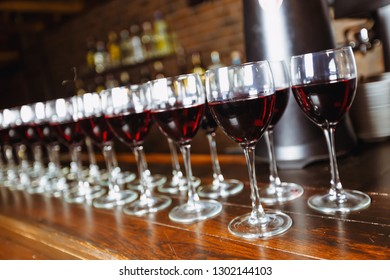 Glasses with red wine are lined up on the bar. welcome drink