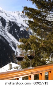 Glasses of red wine on a balcony at a ski resort